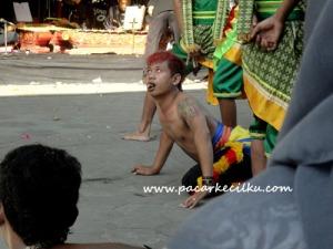 salah seorang penari Jathilan yang lagi kesurupan makan kepala ayam hidup hidup